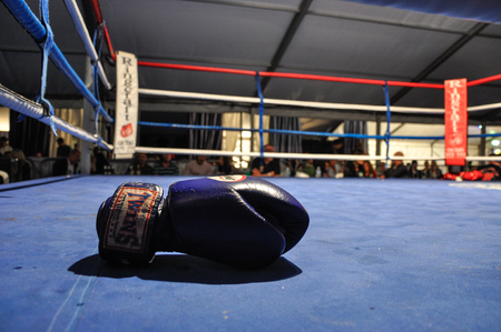 show ring: Sandbank, UK: September 9, 2011 - a boxing glove is on boxing ring after a match during Muay Thai Super Show, Windfest, Sandbank - Poole, UK Editorial