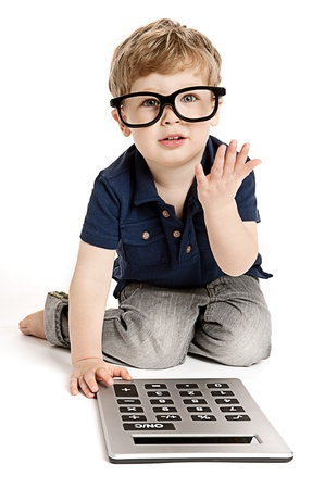 Cute boy wearing bit glasses doing maths with fingers and calculator