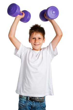 Cute boy lifting weights and smiling. Studio shot on white background. photo