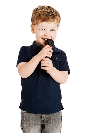Cute boy singing with microphone shot as cutout on studio white background.