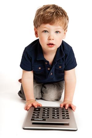Cute boy doing maths with big calculator.