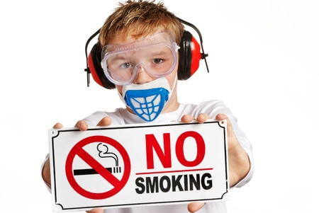 Boy with ear protection and face mask holding no smoking sign. photo