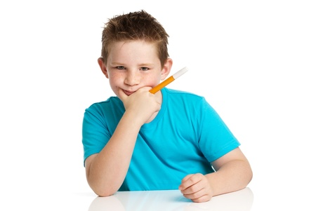 Boy artist thinking with felt pen in hand  Studio white background  photo
