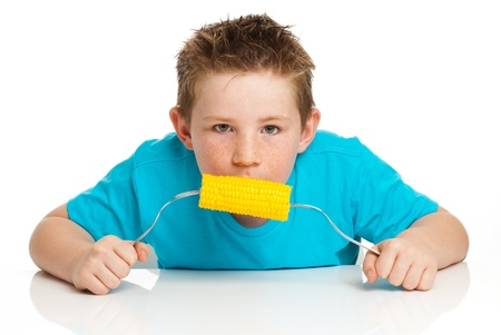 sticking tongue: Boy eating corn on the cob and sticking his tongue out  Studio on white background