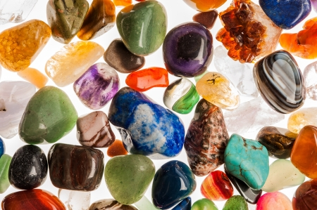 amber coloured: Assortment of polished semi-precious gem stones shot in the studio against white background