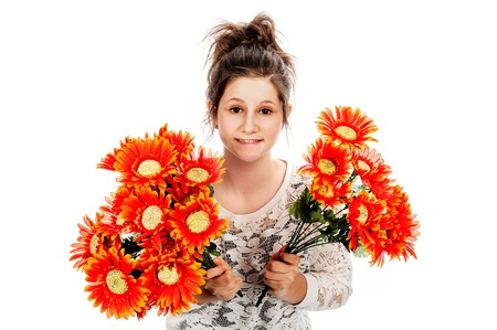 apologise: Guilty looking teenage girl seeking forgiveness with two bunches of fake flowers. Studio shot on white background. Stock Photo