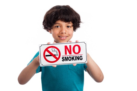 Cute mixed race kid holding no smoking sign. Isolated on white background.