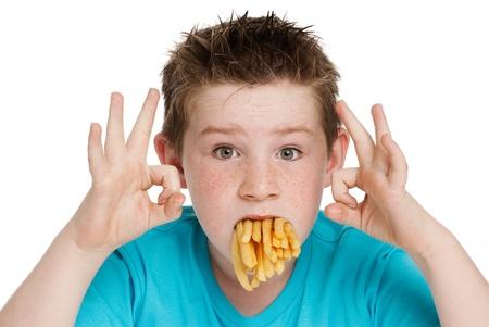 フライド ポテト チップの完全な口を持つ少年。白い背景上に分離。 写真素材