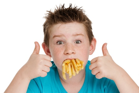 papas fritas: Muchacho joven con la boca llena de virutas fritas. Aislado sobre fondo blanco.