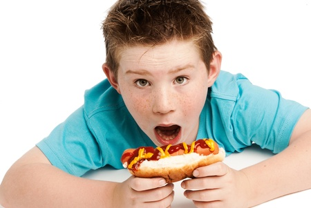spikey: Young boy with spikey hair eating a big hotdog covered in tomatoe ketchup and mustard. Isolated on a white background.