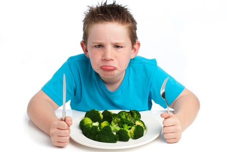 A young boy who is not happy about eating his broccoli. Isolated on white background.