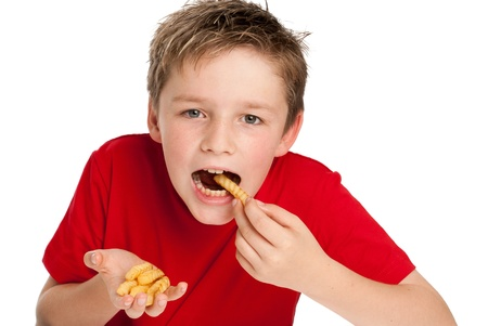 Good looking young boy eating french frie chips. Isolated on white background.