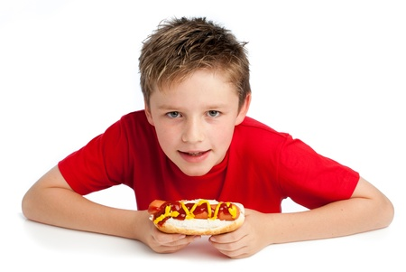 Good looking young boy eating a hoydog with tomato ketchup and mustard. Isolated on white background. photo