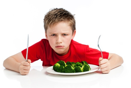 Grumpy young boy with plate of broccoli. Isolated on white background. Standard-Bild