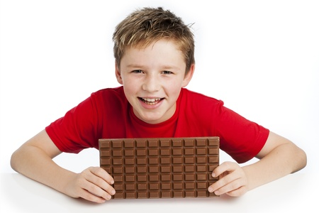 Cute smiling young boy eating a very big bar of chocolate. Wearing a red T-shirt, shot in the studio on a white background. Standard-Bild