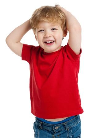 白い背景の上のスタジオで撮影赤の T シャツに満足して少年の笑みを浮かべてください。