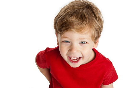 three year old: Cute boy looking up, smiling and laughing, wearing a red T-Shirt in a studio on a white background.