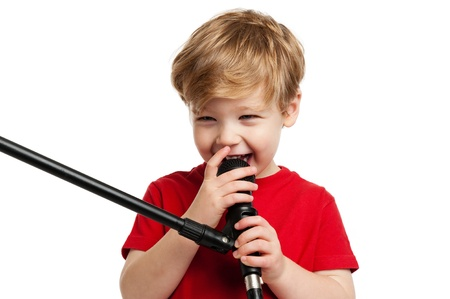 Laughing happy boy singing into a microphone, shot in the studio on a white background. photo