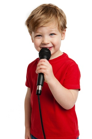 Smiling happy boy singing into a microphone shot in the studio on a white background.