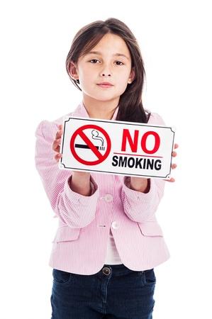 joven fumando: Una hermosa niña de nueve años la celebración de una señal de no fumar. Aislado en un fondo blanco de estudio. Una advertencia y una instrucción.