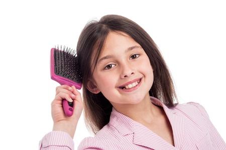 ni�os vistiendose: Adorable chica joven mira a la c�mara mientras se cepillaba el cabello. Aislado sobre fondo blanco de estudio.