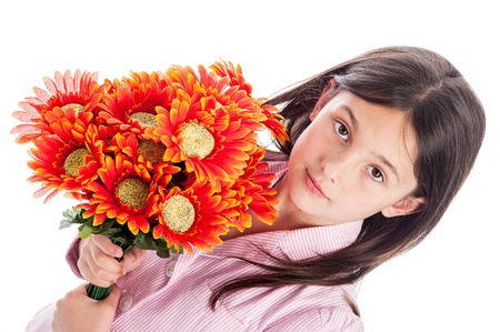 kind hearted: Beautiful young girl looking at camera while holding a bunch of artificial flowers. Isolated on white background. Stock Photo