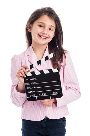 美しい少女は、ムービー メーカー カチンコを押しながらカメラに笑顔します。スタジオの白い背景に分離しました。