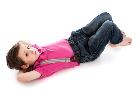 lie down: Trendy young toddler boy, lying down on studio white background. Looking to camera with his hands behind his head. Isolated on a white background.