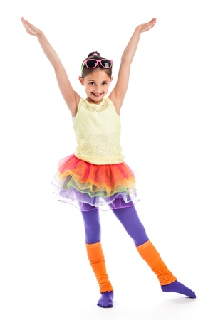Young girl in Colouful cloths. Funky, quirky and trendy. Holding arms up high and wearing sunglasses with leg warmers. Archivio Fotografico