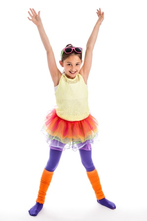 Young girl in Colouful cloths. Funky, quirky and trendy. Holding arms up high and wearing sunglasses with leg warmers. Stock Photo