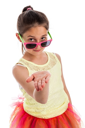 gifting: Quirky young girl with colourful cloths, holding her hand out flat, wearing sun glasses and looking to camera. Isolated on studio white background. Stock Photo