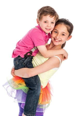 Brother and sister isolated on white studio background. Yound girl is lifting up her brother. Both are smiling and looking happy.