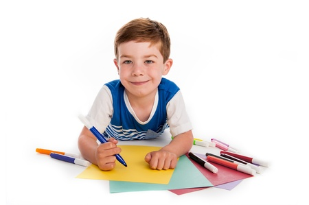 Smiling young boy with felt pens writing and drawing on  colourful paper. White background. photo