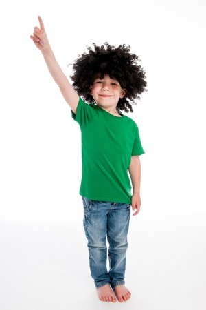 bare feet: Young boy pointing his finger in studio on white background with a big black funny wig. Stock Photo