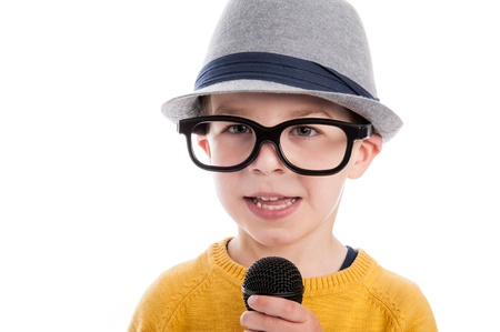 Geeky toddler boy talking in a microphone,  wearing big glasses and a hat. Studio shot isolated on white. photo