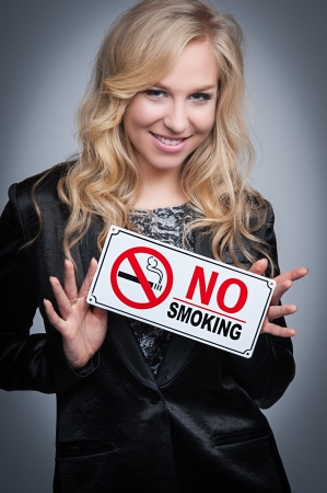 Attractive blond women holding a no smoking sign  photo