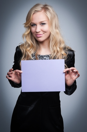Attractive blond women holding a blank paper notice