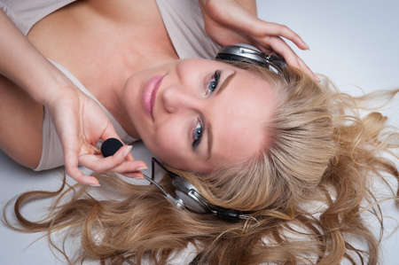 sexy headphones: Woman lying on her back wearing headphones and a microphone  Smiling and looking to camera