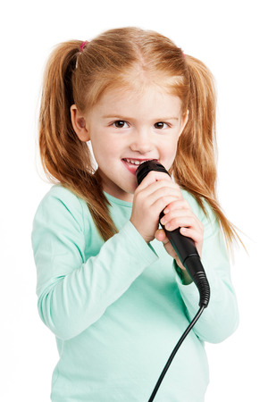 Cute three year old girl singimng with microphone. Archivio Fotografico
