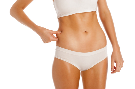 squeeze shape: Thin fitness girl squeezing her body fat  Studio shot isolated on white