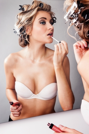 getting ready: Girl in hair curlers applying lipstick while looking in a mirror