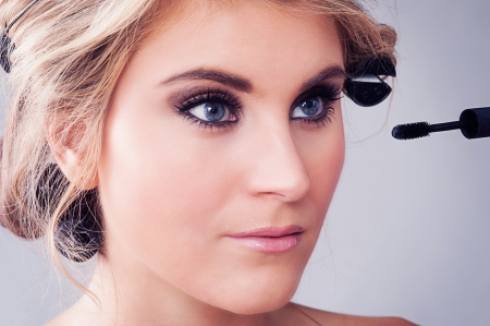 haircurlers: Woman looking in a mirror and applying eye makeup
