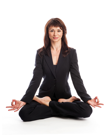 Woman wearing a suit in the Lotus yoga position  Isolated on white  photo