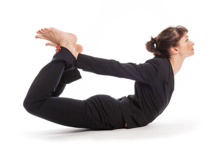 Woman maintaining work life balance in a yoga pose  Shot in studio, isolated on white  photo