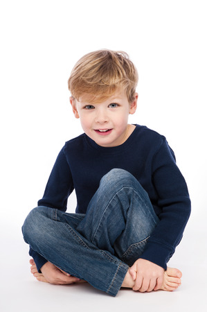 four year old: Four year old boy sitting cross legged. Studio Shot on white background.