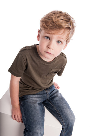 Little boy looking up into camera. Sitting on a box isolated on white studio background. photo