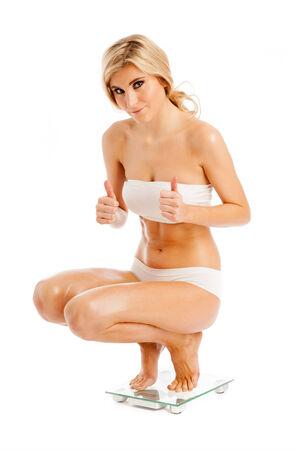 en cuclillas: Mujer feliz con su peso en báscula. Aislado en blanco. Foto de archivo