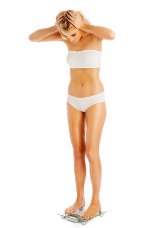 Woman weighing herself on bathroom scales. Studio shot on white . Stock Photo