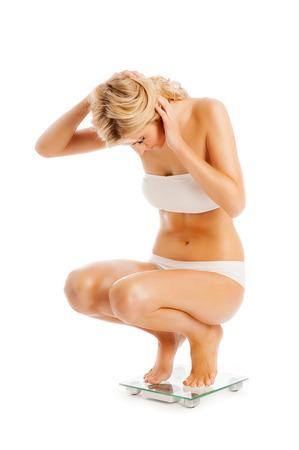 en cuclillas: Slim hermosa mujer que mide su peso en báscula. Aislado en blanco.