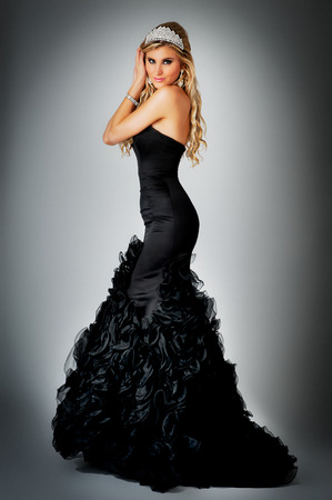 Pageant queen wearing tiara and black ball gown dress